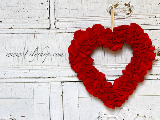 The Valentine Wreath | Lilyshop Blog by Jessie Jane  Materials:  – 1 styrofoam heart shaped wreath from your local craft store – Scissors – 1 yard red felt or 125 3″ Red Felt circles – About 150 1″ Pins – One 12″ piece of ribbon (ivory or red)