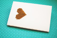 "Embroidered ""knit"" heart notebook Materials:  – sharp needle + something to ""hammer"" it or an awl -pencil -about 3 yards of worsted weight yarn -yarn needle that will fit through the holes you make -graph paper (the paper I used is 5 squares per inch) -card stock or whatever you want to embroider your design on"