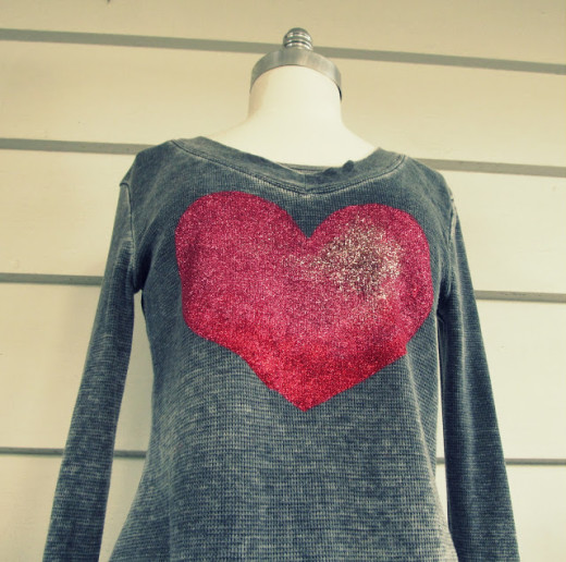 Glitter Heart Tee, DIY | This is a great step by step tutorial how to make this awesome Tee from WobiSobi.  Materials:   –   A Tee of your choice –    A heart stencil* I made mine  –    Masking tape –    Paper Plate –    A piece of Parchment paper or foil –    Three colors of glitter Martha Stewart Glitter in Red *Garnet, Pink* Tourmaline and Light Pink Rose Quartz – Tulip Stencil Sponge   –  Tulip Fabric Paint  in Crimson Red, – Hot Pink and Glacier White.  –    Mod Podge Fabric Glue  Instructions and image credit to the original link  – above the photo.