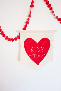 DIY Fabric Valentine  Supplies:  – unbleached muslin – twine – a wooden dowel – 2 colors of craft or fabric paint – sewing machine or needle – paint brush – ribbon – a tag and pen
